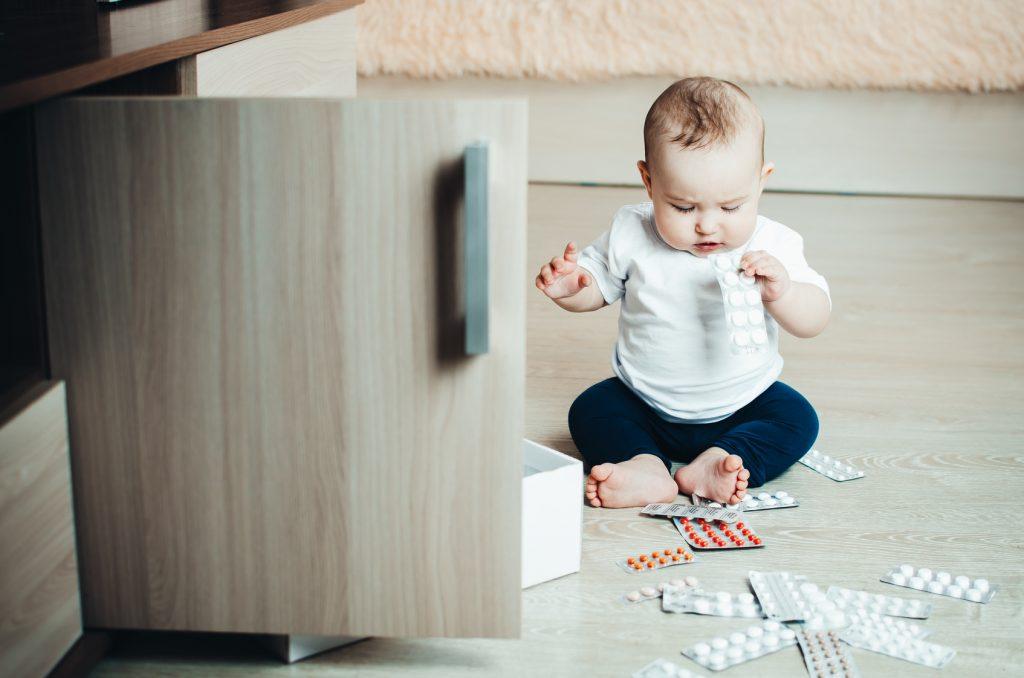 Dziecko przy otwartej szafce z lekami