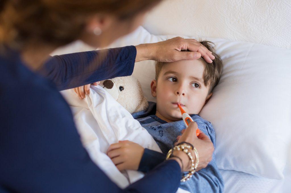 Chory chłopiec mierzy temperaturę