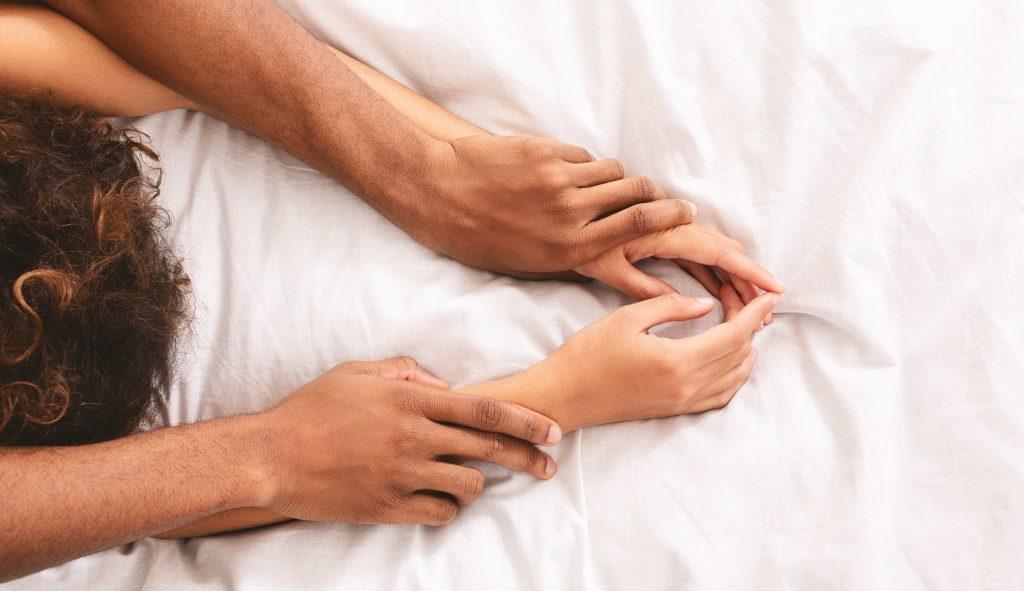 Para trzymająca się w łóżku za ręce