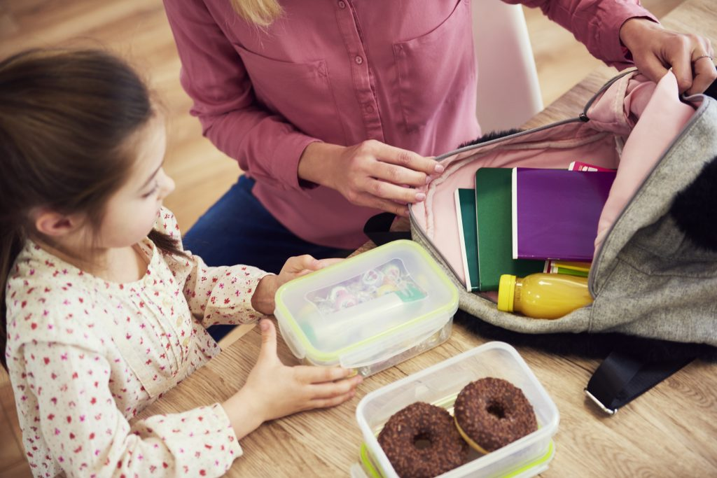 Mama pakuje dziecku drugie śniadanie do szkoły